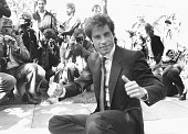 Actor John Travolta giving the thumbs up surrounded by photographers as he adds his hand and foot prints to the cement at Grauman's Chinese Theatre...