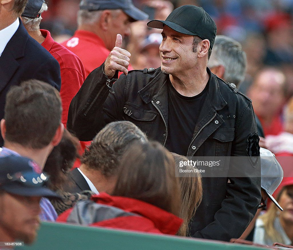 Actor John Travolta had a front row seat near the Boston dugout, here he gives a thumbs up to a fan, Red Sox owner John Henry is at left. The Boston Red Sox take on the Tampa Bay Rays in Game One of the ALDS at Fenway Park.
