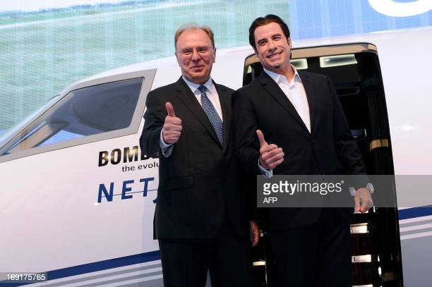 US actor John Travolta poses with Steven Ridolfi president of Canadian Bombardier Business aircraft during a conference to promote the new Challenger...