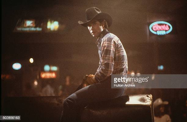 Actor John Travolta rides a mechanical bull in a scene during the Paramount Pictures movie 'Urban Cowboy' circa 1980