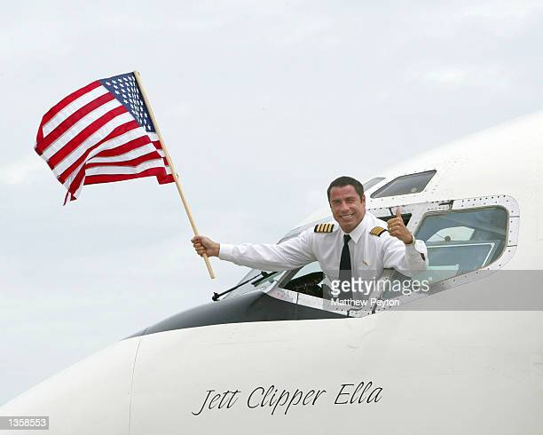 Actor John Travolta waves a flag after arriving in their Quantas 707 'Jett Clipper Ella' on the final stop of his round the globe 'Spirit Of...