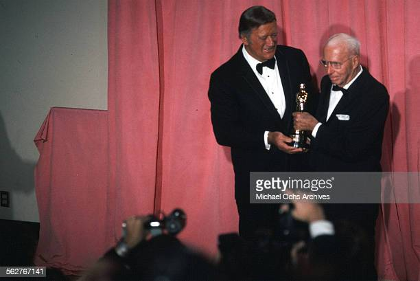 Actor John Wayne and Director Howard Hawks Academy Honorary Award winner pose backstage during the 47th Academy Awards at Dorothy Chandler Pavilion...
