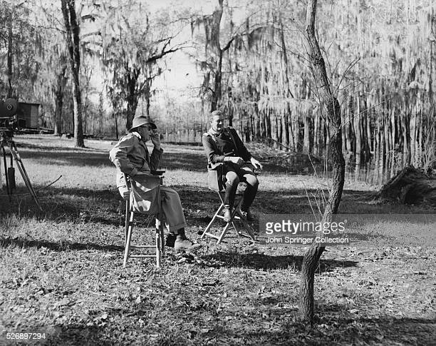 Actor John Wayne and Director John Ford sit and talk while on location for the film The Horse Soldiers
