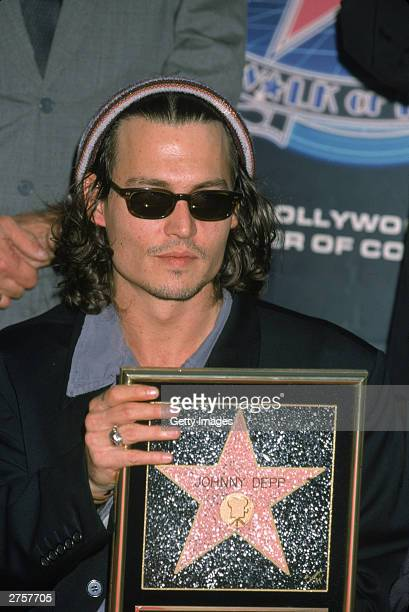 Actor Johnny Depp holds a replica of his star on the Hollywood Walk of Fame 1994