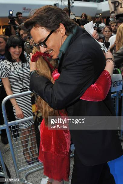 Actor Johnny Depp hugs School girl Beatrice Delap as he arrives for the UK Premiere of 'Pirates Of The Caribbean On Stranger Tides' at Vue Westfield...