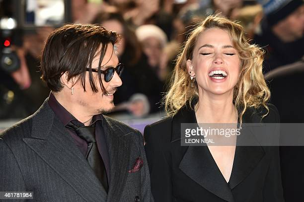 US actor Johnny Depp jokes with fiancee US actress and model Amber Heard as they arrive for the UK premiere of the film 'Mortdecai' in London on...