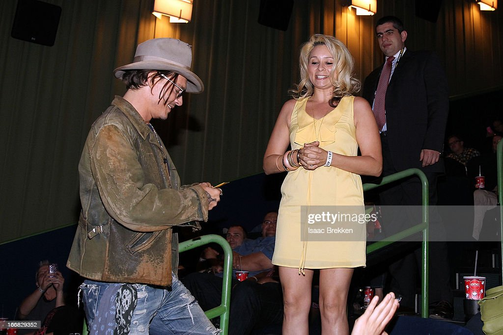 Actor <a gi-track='captionPersonalityLinkClicked' href=/galleries/search?phrase=Johnny+Depp&family=editorial&specificpeople=202150 ng-click='$event.stopPropagation()'>Johnny Depp</a> receives a gift from a fan in the audience at 'The Lone Ranger' fan event and global trailer launch at the AMC Town Square 18 theatres on April 17, 2013 in Las Vegas, Nevada.