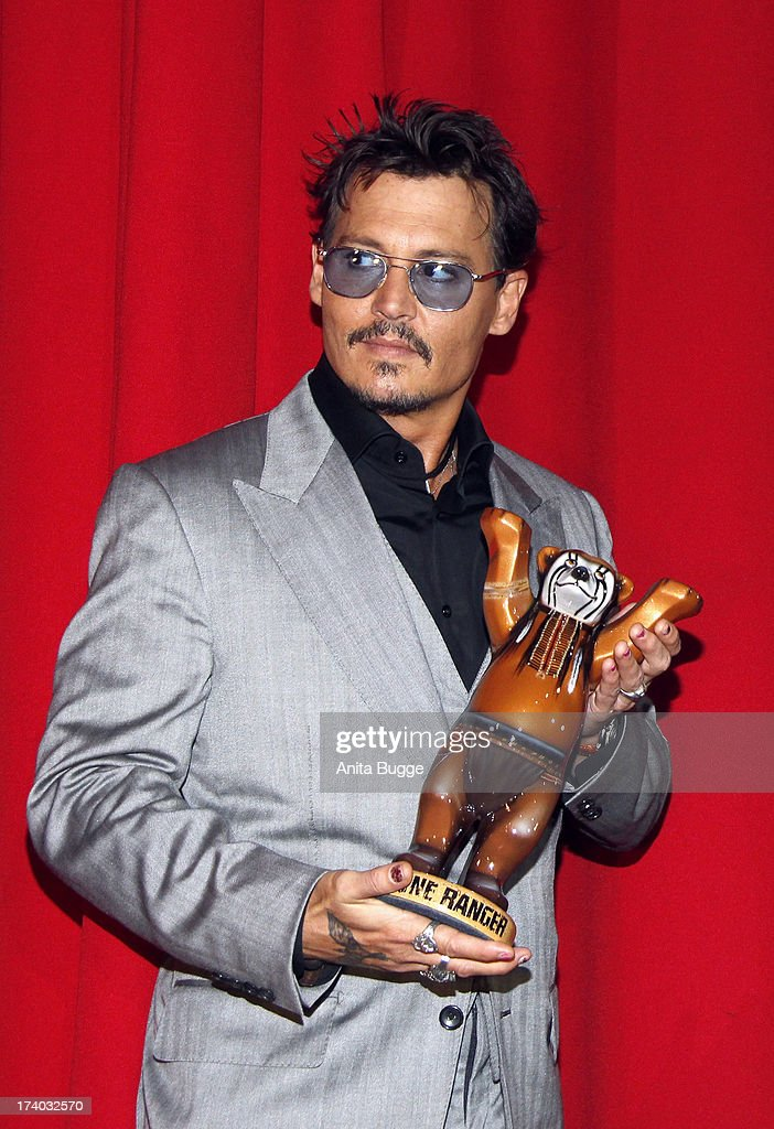 Actor <a gi-track='captionPersonalityLinkClicked' href=/galleries/search?phrase=Johnny+Depp&family=editorial&specificpeople=202150 ng-click='$event.stopPropagation()'>Johnny Depp</a> receives a 'Lone Ranger Berlin Bear' during the 'Lone Ranger' Germany premiere at Sony Centre on July 19, 2013 in Berlin, Germany.