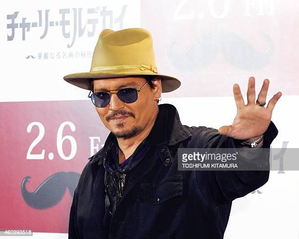 US actor Johnny Depp waves during his photo call in Tokyo on January 28 2015 Depp attended the Japan premiere of his latest action comedy movie...