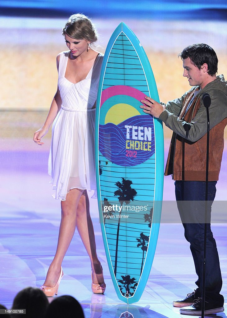 Actor Josh Hutcherson (R) accepts the Choice Movie Sci-Fi/Fantasy Actor award from musician Taylor Swift onstage during the 2012 Teen Choice Awards at Gibson Amphitheatre on July 22, 2012 in Universal City, California.