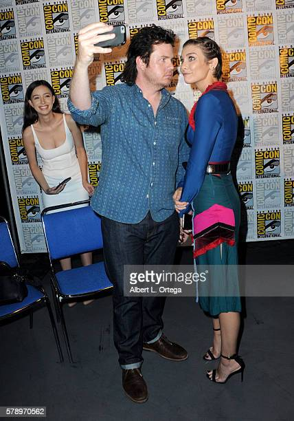 Actor Josh McDermitt takes a selfie with actress Lauren Cohan as actress Christian Serratos looks on at AMC's 'The Walking Dead' panel during...