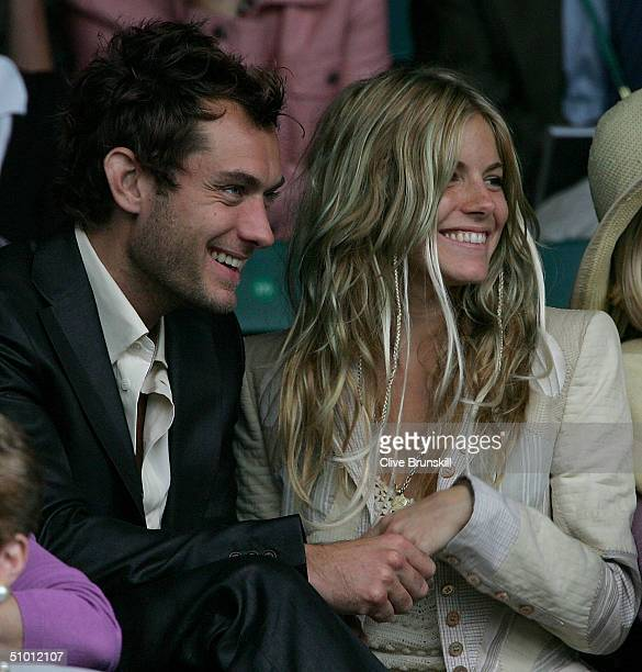 Actor Jude Law and actress Sienna Miller watch the quarter final match between Tim Henman and Mario Ancic of Croatia at the Wimbledon Lawn Tennis...