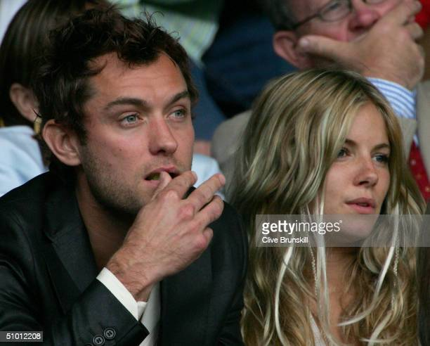 Actor Jude Law and actress Sienna Miller watch the quarter final match between Lleyton Hewitt of Australia and Roger Federer of Switzerland at the...