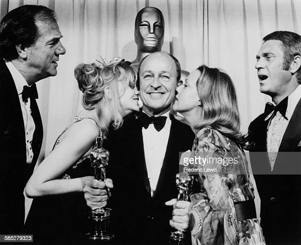 Actor Karl Malden getting a kiss from actresses Goldie Hawn and Jeanne Moreau watched by actors Steve McQueen and Frank McCarthy at the 42nd Academy...