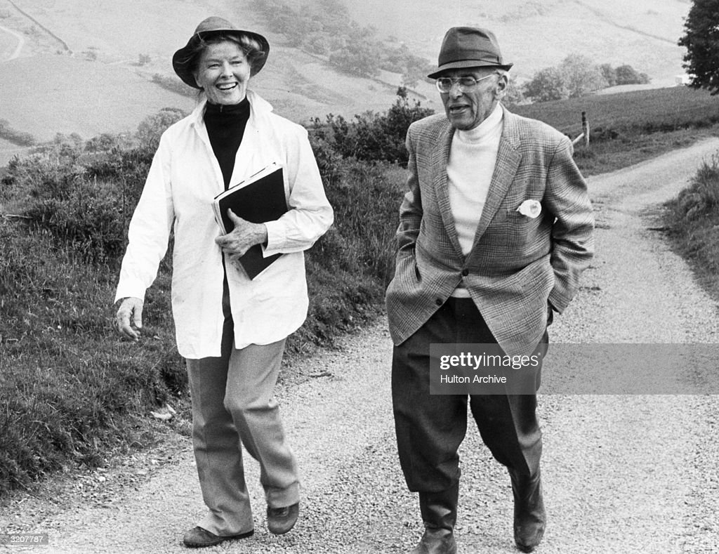 Actor Katharine Hepburn (1907 - 2003) and director George Cukor take a walk on a road between takes of the television movie 'The Corn is Green', the tenth and last film Hepburn and Cukor collaborated on, South Wales.