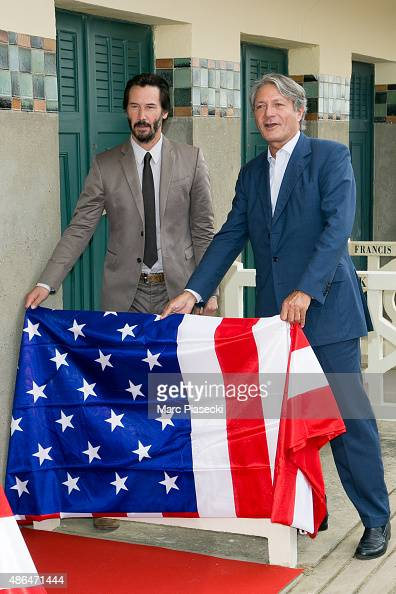 Actor Keanu Reeves and Mayor of Deauville Philippe Augier pose next to the beach closet dedicated to him during a photocall on September 4 2015 in...