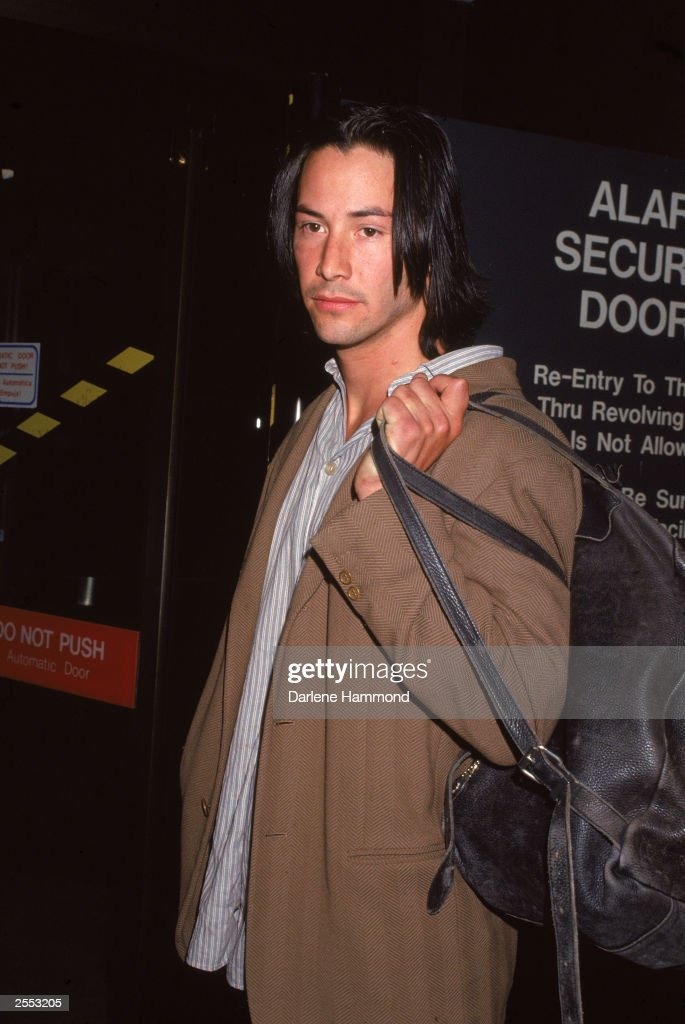 Actor Keanu Reeves holds a bag over his shoulder, c. 1993.