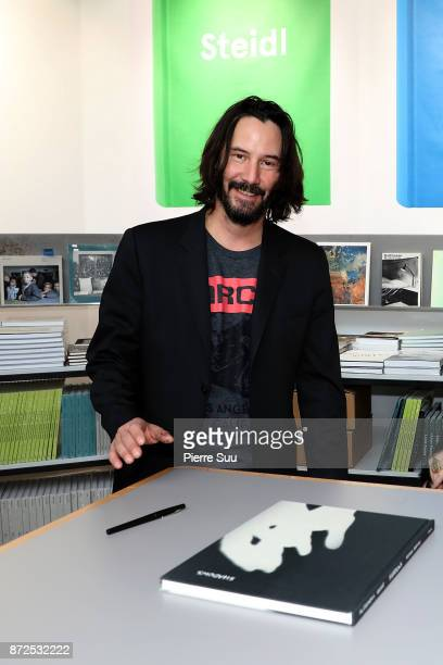 Actor Keanu Reeves is seen posing by his book 'Ode to happiness' during 'Paris Photo' at le Grand Palais on November 10 2017 in Paris France