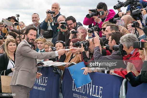 Actor Keanu Reeves signs autographs after posing next to the beach closet dedicated to him during a photocall on September 4 2015 in Deauville France