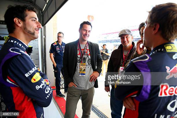 Actor Keanu Reeves speaks with Sebastian Vettel of Germany and Infiniti Red Bull Racing and Daniel Ricciardo of Australia and Infiniti Red Bull...