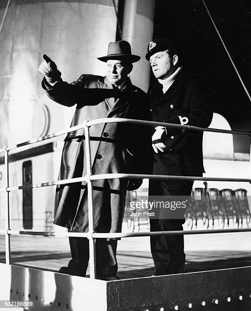 Actor Kenneth More in costume as Second Officer Lightoller talking to 'Titanic' ship wreck survivor Gus Cohen on the deck of the model replica of the...