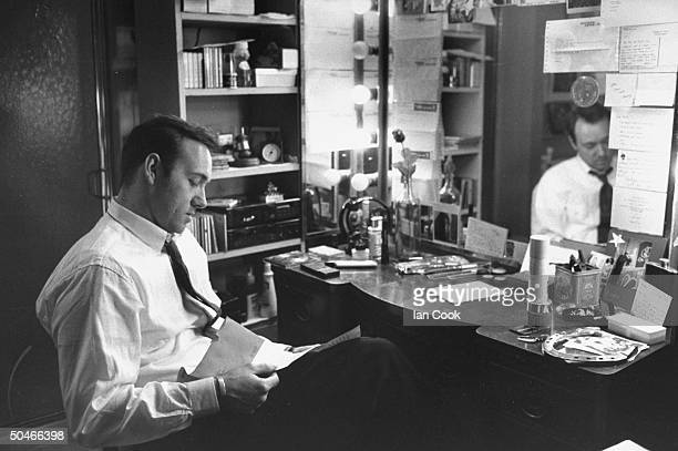 Actor Kevin Spacey reading letter as he sits at table in front of mirror in his dressing room at the Richard Rodgers Theater where is performing in...