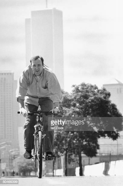 Actor Kevin Spacey riding bicycle on street nr Westside Highway