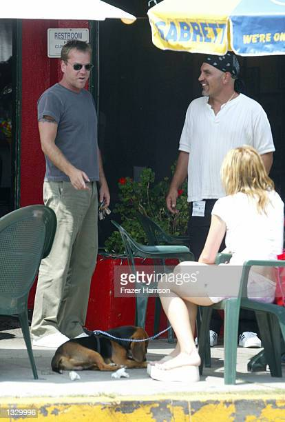 Actor Kiefer Sutherland talks with unidentified friends after eating at Albano's Brooklyn Pizzeria on August 3 2002 in Los Angeles California