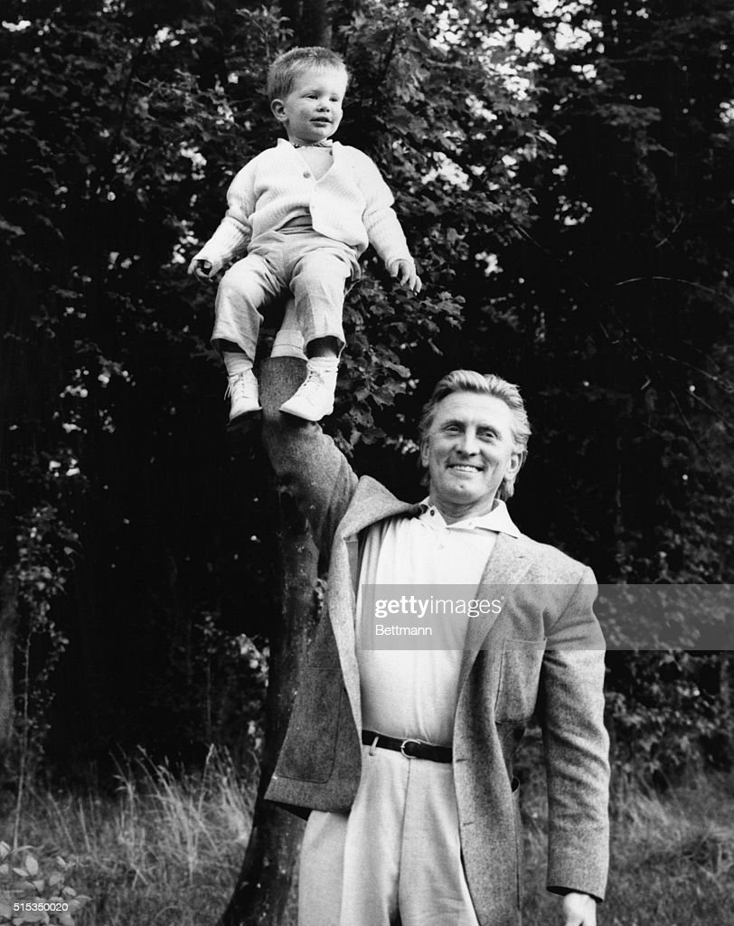 Actor Kirk Douglas demonstrates his strength and 21month old Peter Vincent Douglas his bravery as father hoists son aloft for the cameraman The actor...