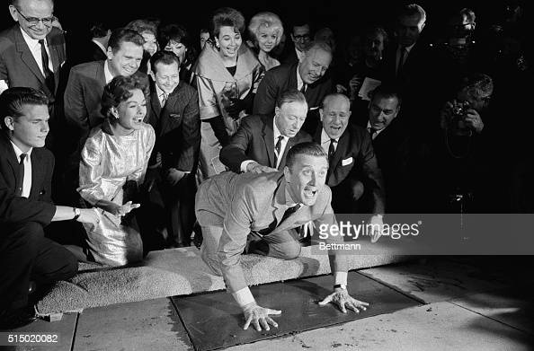 Actor Kirk Douglas in obvious high spirits puts his hands in the cement in front of Grauman's Chinese Theater November 1st At right bandleader Ken...