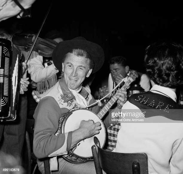 Actor Kirk Douglas plays the banjo during a party in Los Angeles California