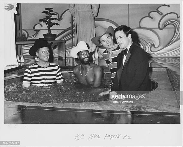 Actor Larry Hagman singer Teddy Pendergrass and comedians Sid Caesar and Jeff Altman sitting together in a hot tub in a skit from the show 'Pink...