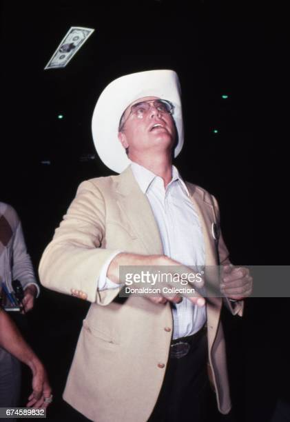 Actor Larry Hagman throws hundred dollar bills at an event in September 1980 in Los Angeles California