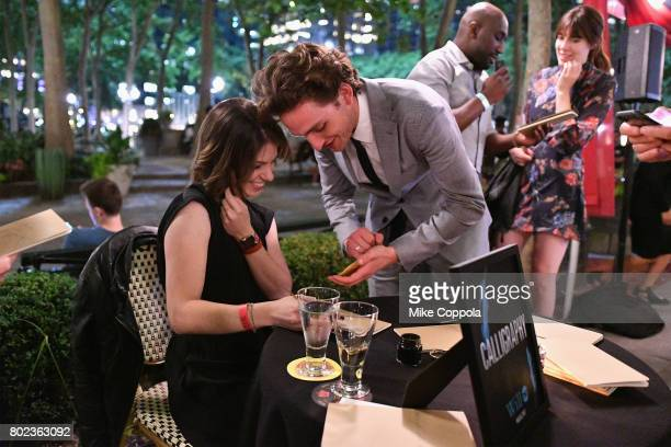Actor Laurie Davidson asks calligrapher Sam Teich for a custom message on a notebook during TNT's Season One 'Will' Premiere After Party at Bryant...