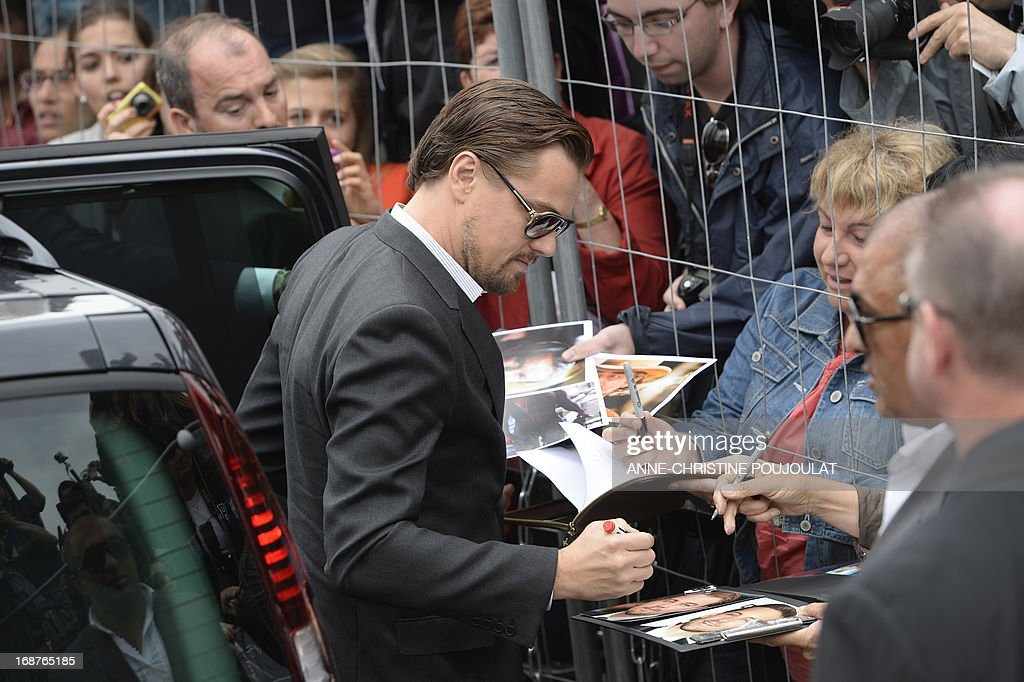 US actor Leonardo DiCaprio signs autographs as he arrives on May 15, 2013 for a photocall for 'The Great Gatsby' ahead of the opening of the 66th edition of the Cannes Film Festival on May 15, 2013 in Cannes. Cannes, one of the world's top film festivals, opens on May 15 and will climax on May 26 with awards selected by a jury headed this year by Hollywood legend Steven Spielberg.