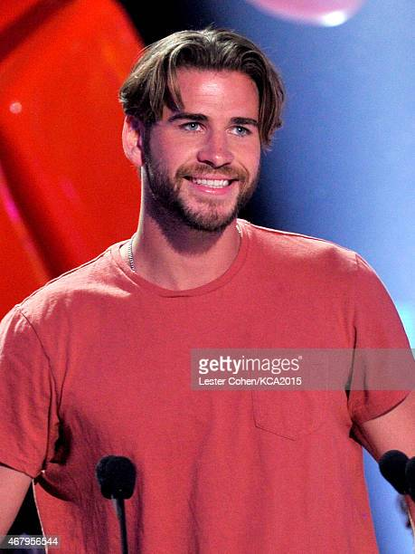 Actor Liam Hemsworth accepts Favorite Male Action Star for 'The Hunger Games Mockingjay Part 1' with actor Kevin James onstage during Nickelodeon's...