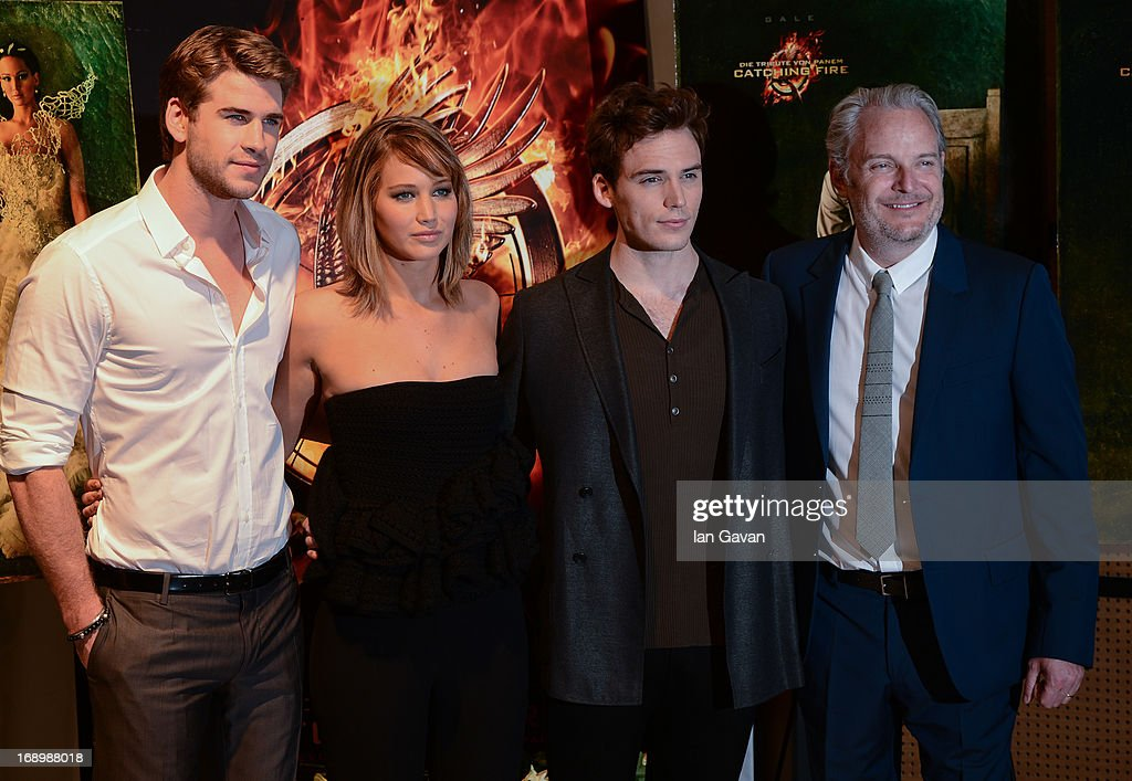 Actor <a gi-track='captionPersonalityLinkClicked' href=/galleries/search?phrase=Liam+Hemsworth&family=editorial&specificpeople=6338547 ng-click='$event.stopPropagation()'>Liam Hemsworth</a>, actress <a gi-track='captionPersonalityLinkClicked' href=/galleries/search?phrase=Jennifer+Lawrence&family=editorial&specificpeople=1596040 ng-click='$event.stopPropagation()'>Jennifer Lawrence</a>, actor <a gi-track='captionPersonalityLinkClicked' href=/galleries/search?phrase=Sam+Claflin&family=editorial&specificpeople=7238693 ng-click='$event.stopPropagation()'>Sam Claflin</a> and director <a gi-track='captionPersonalityLinkClicked' href=/galleries/search?phrase=Francis+Lawrence&family=editorial&specificpeople=224820 ng-click='$event.stopPropagation()'>Francis Lawrence</a> pose at the 'The Hunger Games: Catching Fire' photocall during The 66th Annual Cannes Film Festival at Nespresso Beach on May 18, 2013 in Cannes, France.