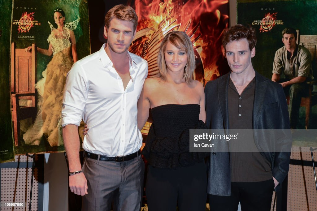 Actor Liam Hemsworth, actress Jennifer Lawrence and actor Sam Claflin pose at the 'The Hunger Games: Catching Fire' photocall during The 66th Annual Cannes Film Festival at Nespresso Beach on May 18, 2013 in Cannes, France.