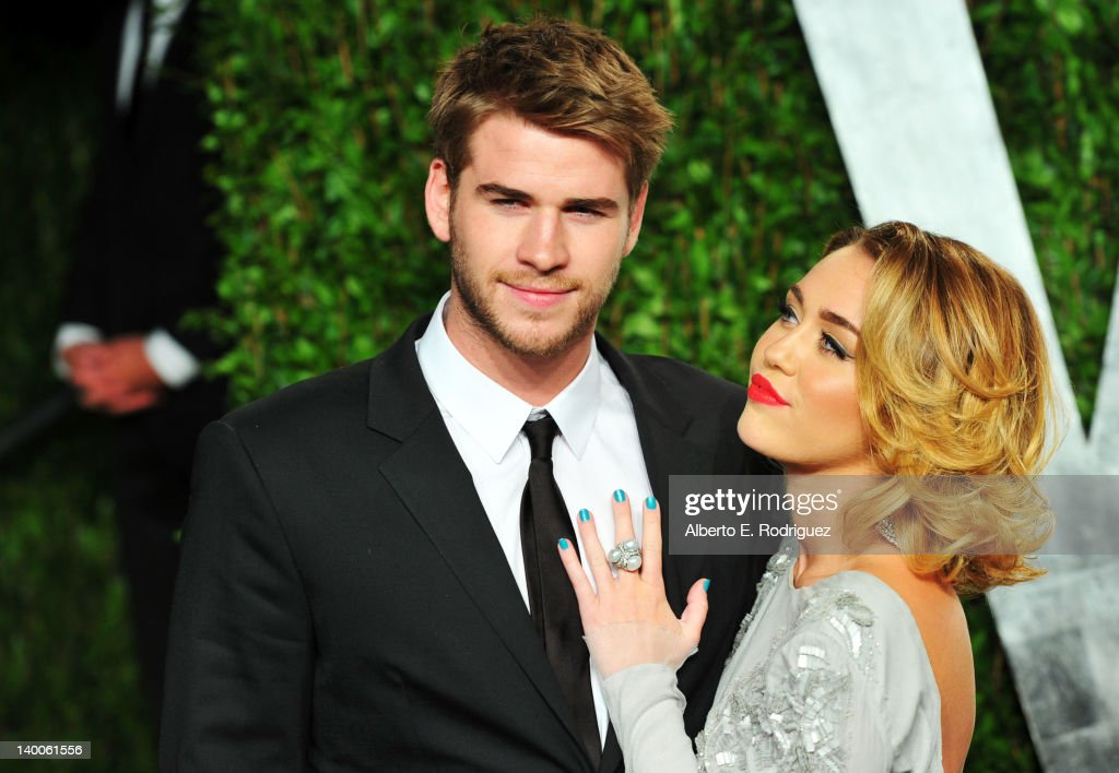 Actor Liam Hemsworth (L) and entertainer Miley Cyrus arrive at the 2012 Vanity Fair Oscar Party hosted by Graydon Carter at Sunset Tower on February 26, 2012 in West Hollywood, California.