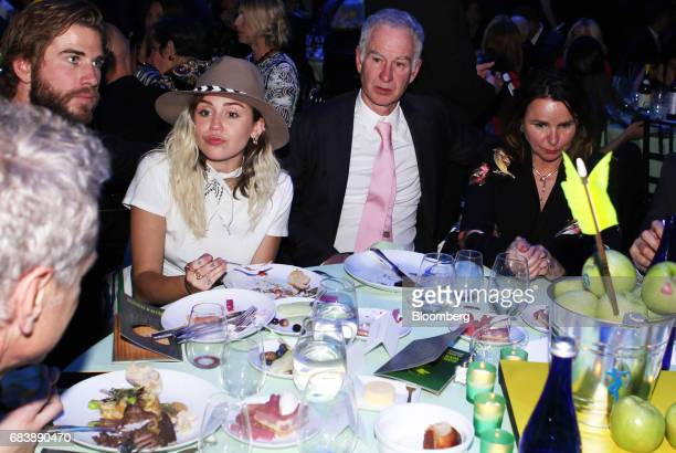 Actor Liam Hemsworth from left singer Miley Cyrus former professional tennis player John McEnroe and singersongwriter Patty Smyth sit at a table...