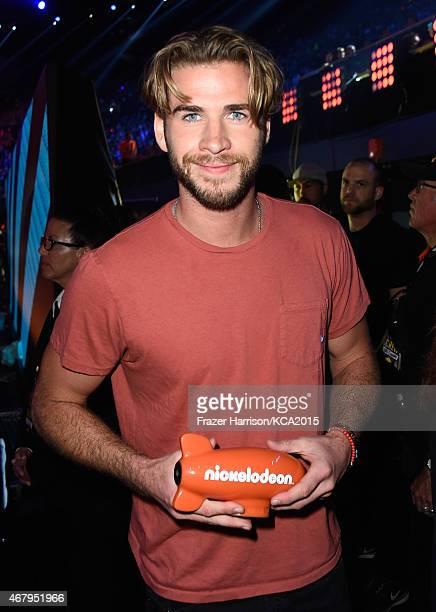 Actor Liam Hemsworth poses with the Favorite Male Action Star award for 'The Hunger Games Mockingjay Part 1' backstage during Nickelodeon's 28th...