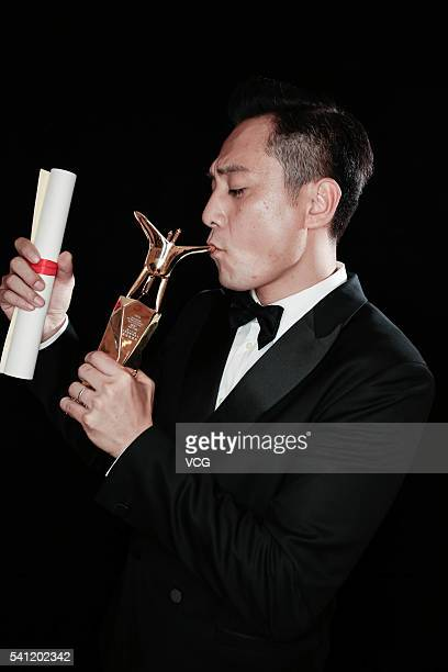 Actor Liu Ye poses with the trophy during the award ceremony of 19th Shanghai International Film Festival at Shanghai Grand Theatre on June 19 2016...