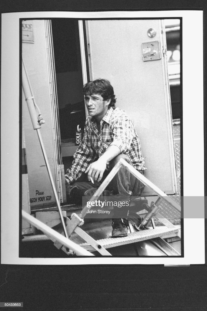 Actor Luke Perry holding lit cigarette as he sits on steps outside his dressing rm., during a break in the filming of the movie 8 Seconds.