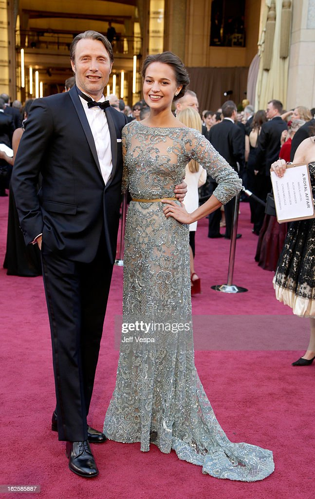 Actor Mads Mikkelsen (L) and Alicia Vikander arrive at the Oscars at Hollywood & Highland Center on February 24, 2013 in Hollywood, California.