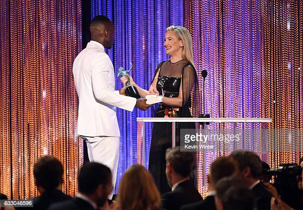 Actor Mahershala Ali accepts Outstanding Performance by a Male Actor in a Supporting Role for 'Moonlight' from actor Kate Hudson onstage during The...