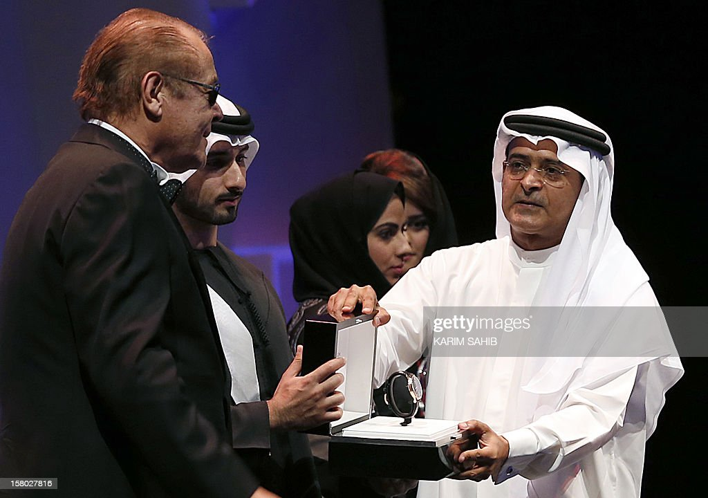 Actor Mahmud Abdel Aziz receives a IWC watch, as part of the Lifetime Achievement award presentated by Sheikh Mansur bin Mohammed bin Rashid al-Maktoum at the Dubai International Film Festival in the Gulf emirate of Dubai, on December 9, 2012. AFP PHOTO/KARIM SAHIB
