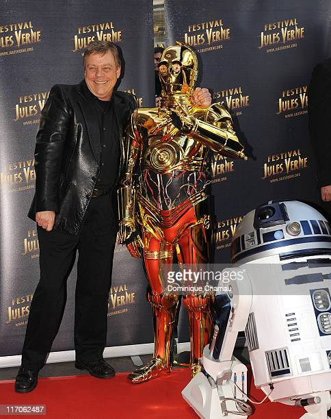 Actor Mark Hamill poses with C3PO and R2D2 as he attends 30th Anniversary Tribute to 'Star Wars Episode V The Empire Strikes Back' during the Jules...