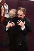Actor Mark Rylance embraces director Steven Spielberg after winning the Best Supporting Actor award for 'Bridge of Spies' during the 88th Annual...