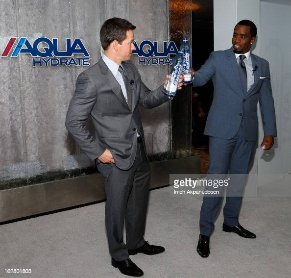 Actor Mark Wahlberg and producer/entrepreneur Sean Combs toast onstage while hosting a press conference to announce their newest venture Water Brand...