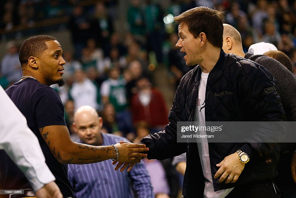Actor Mark Wahlberg greets Patrick Chung #27 of the New England Patriots while attending the game between the Boston Celtics and the Philadelphia 76ers during the game on December 8, 2012 at TD Garden in Boston, Massachusetts.
